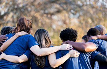team huddle hands on shoulders